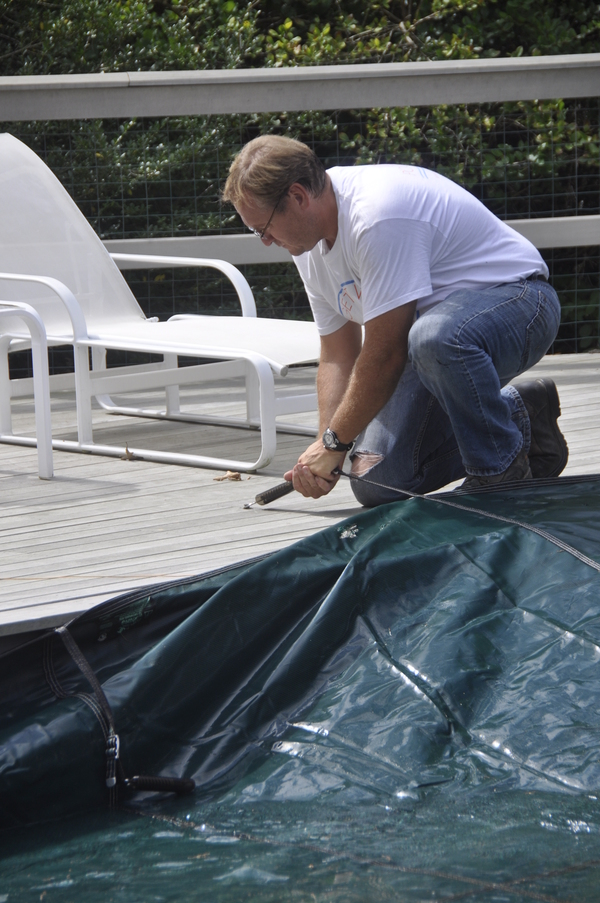 John's Pools & Spas executive manager Stanley Schorr covers a pool in Quogue.