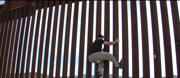 Dennis Michael Lynch grabs ahold of the fence separating Mexico from Arizona. COURTESY DENNIS MICHAEL LYNCH