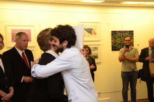 Jesse Warren hugs Southampton Village Deputy Clerk Eileen Musarra after being declared the winner of the mayoral race on Friday. GREG WEHNER