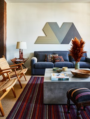 In this 1880s converted loft, note the richly layered history of the mid-century side table, recently reupholstered antique footstool with vintage kilim upholstery to complement the kilim pillows on the sofa, and the vessels on the coffee table from unknown periods. CHRISTIAN HARDER