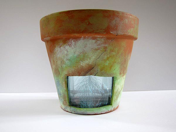 Terra cotta pot by Nicolette Jelen. The glass and mirror insert is etched with tree branches that can be seen through the window in the pot. COURTESY ALEXANDRA EAMES