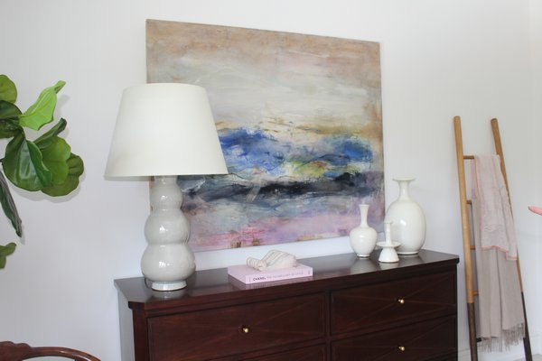 An abstract painting by East Hampton artist Anne Raymond is featured in the bedroom curated by Kate Singer Home.  JULIA HALSEY