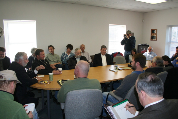 U.S. Representative Tim Bishop, second from left,  listens to concerns from farmers at the  Long Island Farm Bureau on Saturday. Headquarters In Calverton.