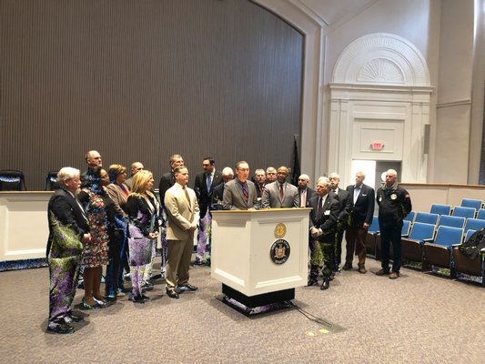 New York State Senator James Gaughran speaking during a rally at Huntington Town Hall calling for the restoration of AIM funding in the state budget. Behind him are various town supervisors and village mayors. COURTESY OFFICE OF ASSEMBLYMAN FRED THIELE