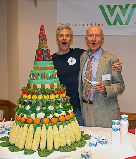 Rip Esselstyn, author of The Engine 2 Diet, stands with Doug Mercer, founder of the Wellness Foundation in front of the Engine 2 food pyramid, made of just fruits and vegetables.