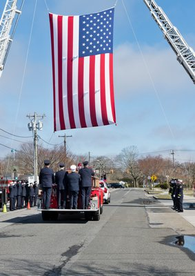 The funeral procession for Westhampton Beach Fire Department member Don Griffin passes by the firehouse on Saturday morning. COURTESY WESTHAMPTON BEACH FIRE DEPARTMENT