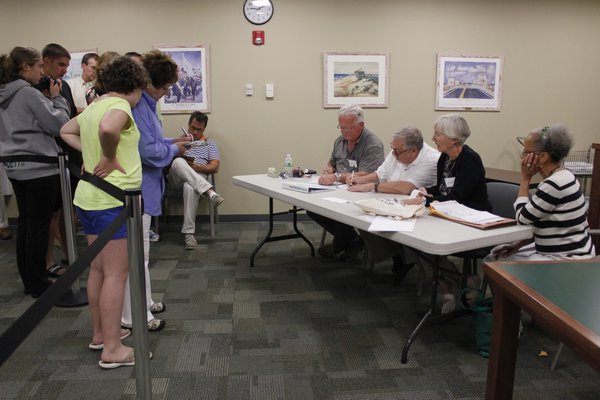 Surrounded by family and friends, the candidates for the Westhampton Beach Board of Trustees await the results of the election while officials tally the votes. BY CAROL MORAN