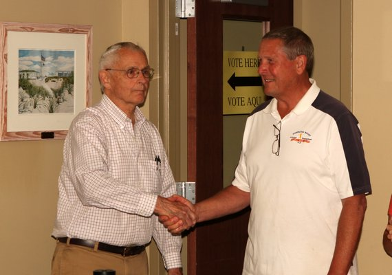 June 26 -- Ousted Westhampton Beach Mayor Conrad Teller, left, congratulates Village Trustee Ralph Urban on his win.