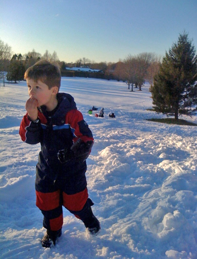 Tristan Sabbeth stops for a mouthful of snow between sled raced in Bridgehampton.