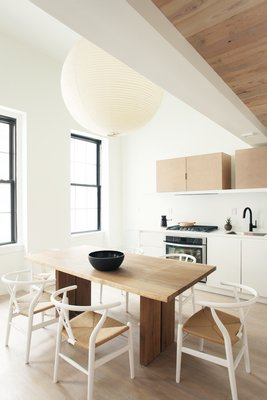 Wood tones in a limited color palette were kept with the flooring in mind to provide a warm backdrop and as grounding element to counterpoint the whites throughout. There are little hints of greenery at a home on Weybosset Street in Providence, Rhode Island. CHRISTIAN HARDER
