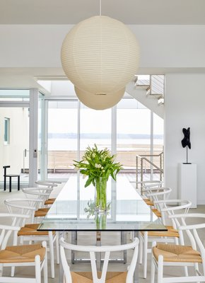 The dining room showcases a glass top table to reflect the bay view to the north, and natural cord seats to complement the marshland grasses beyond. CHRISTIAN HARDER