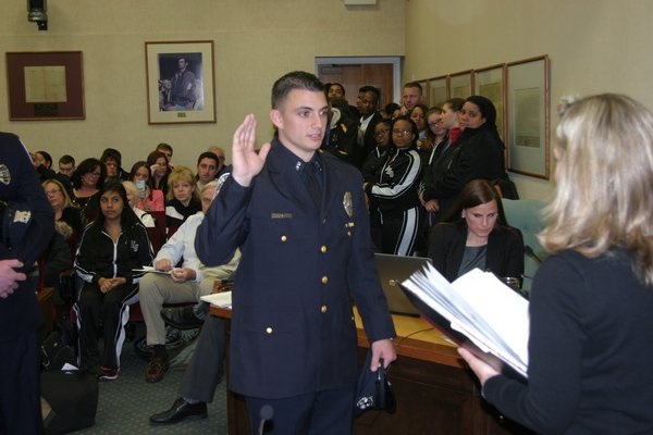 Newly hired and newly promoted police officers were sworn in at Town Hall on Tuesday night. M. Wright