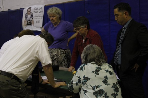 Officials from the East Quogue School District look on as the absentee ballots are tallied Tuesday night. BY CAROL MORAN