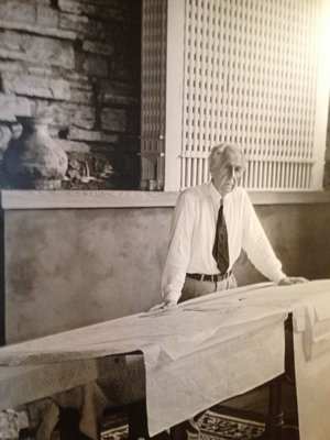 Frank Lloyd Wright in his Taliesin East Studio with the model of the San Francisco Call Building of 1913, which is included in the MoMA exhibition.
