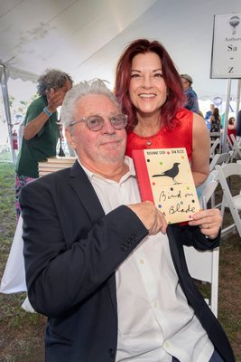 Dan Rizzie and Roseanne Cash with their book Bird on a Blade during the East Hampton Library's 15th Annual Authors Night Benefit under the tent at 555 Montauk Highway in Amagansett on Saturday.