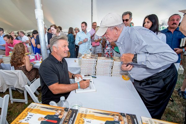 Alec Baldwin chats with a patron as he signs a copy of his book for him during the East Hampton Library's 15th Annual Authors Night Benefit under the tent at 555 Montauk Highway in Amagansett on Saturday.