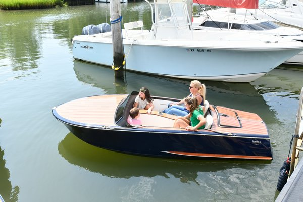 Sustainable Southampton Green Advisory Committee member Victoria Gorman takes Christopher and Isabella Glorioso and her daughter Marchella out for ride in the electric runabout boat. DANA SHAW