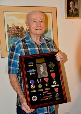 Martin Sylvester at his home in Springs, holding his war awards.  Medals: Purple Heart, Prisoner of War, Bronze Star, Legion of Honor, N.Y.S. Distinguished Service Medal.       Ribbons: WWII Victory, Good Conduct, European Theater, Three Battle Stars.  Other: Unit Citation, Combat Infantry Badge, Ivy Leaf Patch (4th Infantry)