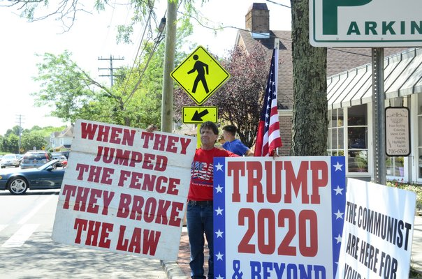 President Trump protesters and supporters lined Montauk Highway in Water Mill on Friday, in anticipation that he would eventually drive by. GREG WEHNER