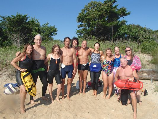 A happy crew after another excellent open water swim workout, framed by coaches Anita LaGrassa, far left, and Tim Treadwell, far right.