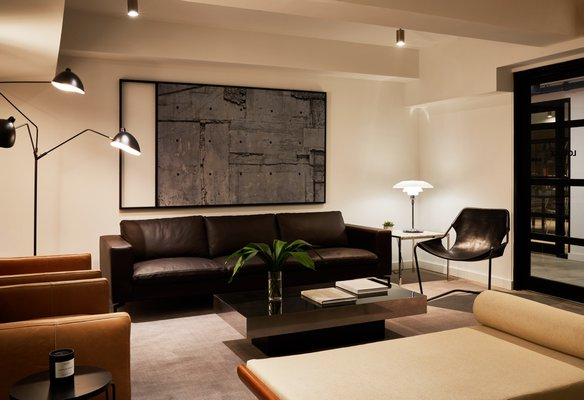 A cellar-level lounge in Brooklyn showing a combination of hardwired semi-flush mount spotlights, a Poul Henningsen table lamp and a three-arm Serge Mouille floor lamp.