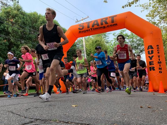 Kal Lewis, front and center at the start of Sunday's Ellen's Run 5K, finished first overall despite a pair of missed turns on a hot and humid day on the roads around Stony Brook Southampton Hospital.