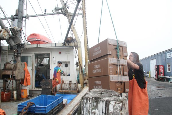 Fishermen unloading the catch from a commercial fishing boat at Shinnecock Fish Dock in Hampton Bays.