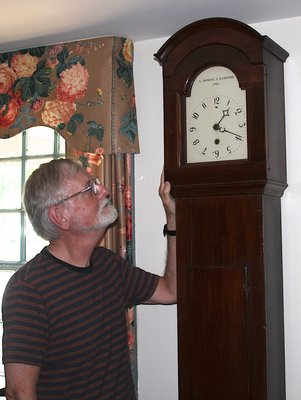 Richard Barons, chief curator of the East Hampton Historical Society at the Jackson Osborn House next to a Dominy clock.   KYRIL BROMLEY
