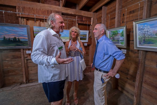 Michael Daly, Michelle Seitz and Jay Schneiderman converse during the annual Peconic Land Trust Gala at the Ocean View Farm in Bridgehampton on Sunday evening.