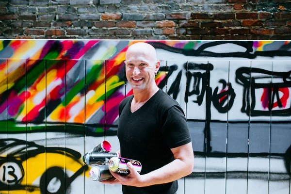 Artist Mitchell Schorr at a New York City event with one of his murals in the background.