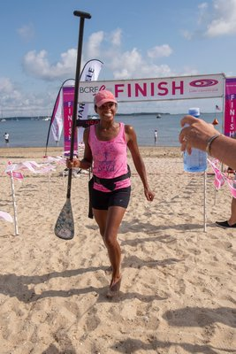3-Mile First Place Female Winner Taryn Berkett (with a time of 43:41) crosses the finish line during the annual Paddle for Pink at Havens Beach on Saturday morning.