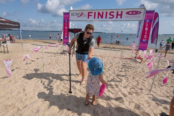 Matthew Plourde accepts a bottle of water from 2-1/2-year-old Mia Pardo as he crosses the finish line during the annual Paddle for Pink at Havens Beach on Saturday morning.