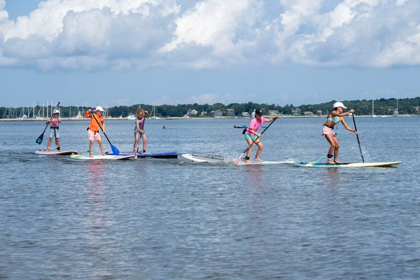Kids participate in the children's paddleboard race during the annual Paddle for Pink at Havens Beach on Saturday morning.