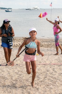 Alice Geirsson, 11, crosses the finish line as the winner of the children's paddleboard race during the annual Paddle for Pink at Havens Beach on Saturday morning.