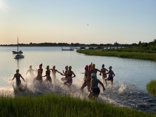 The girls enter the water to start the triathlon.