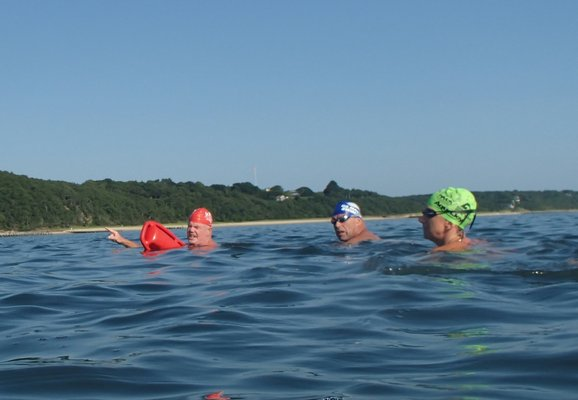 "Coach Tim Treadwell explains the next swim course and ""sighting"" tricks to prevent wandering off course."