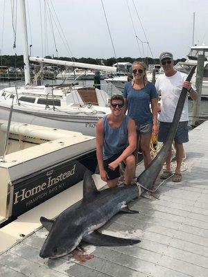 Ian Keller, Laura Zaweski and John Zaweski with a 186-pound thresher shark they caught 12 miles south of Shinnecock Inlet last week.  Courtesy of Tracy Zaweski