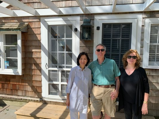 Sylvia Wong, left, who works at the firm that recently bought The Gansett Green Manor stands with Jed and Leslie Feldman, previous owners.        BEN KAVA