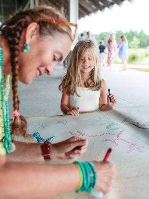 Artist Bastienne Schmidt assisting a girl in art at the Summer Family Party.