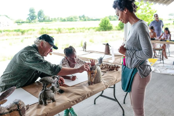 Artist Paton Miller assisting a girl in crafts at the Summer Family Party.