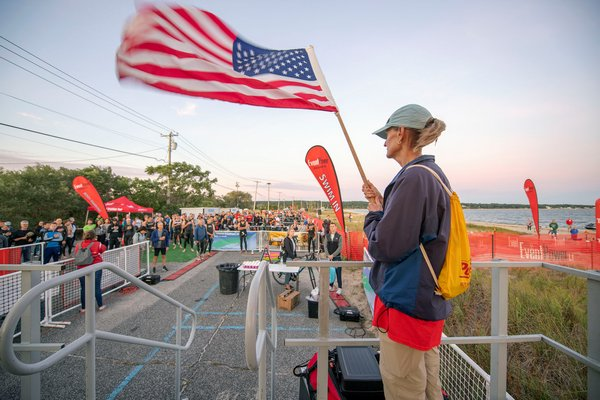 Wendy Barrick holds the American flag for the National Anthem at the start of the 38th Annual Mighty Hamptons Triathlon on Long Beach on Sunday morning.