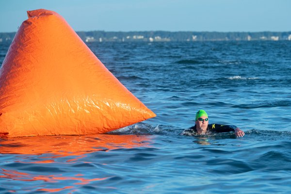 Austin Quinn of New York City rounds the buoy as the first swimmer to finish the swimming leg of the 38th Annual Mighty Hamptons Triathlon.