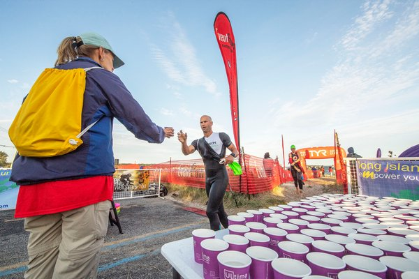 Wendy Barrick hands out cups of water to finishers of the swimming leg.
