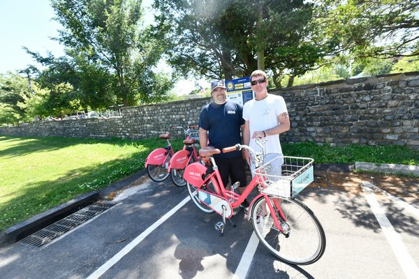 Chris Dimon and Patrick O'Donoghue at the Pedalshare station at Agawam Park in Southampton Village in July. DANA SHAW