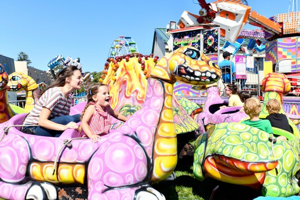 Kathleen Comber and Niama Kelly take a ride on a dinosaur at the San Gennaro Fest or the Hamptons on Saturday.
