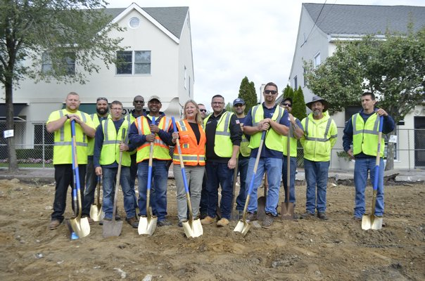 Village Mayor Maria Moore and Department of Public Works Superintendent Matthew Smith, center, with DPW crew. ANISAH ABDULLAH