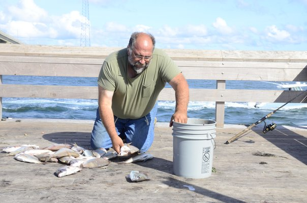 Paul Ripperger of West Islip counted the number of porgie he caught from the Old Ponquogue Bridge Pier on Friday morning. GREG WEHNER