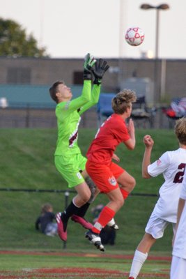 Southampton goalie Ashton Triffin goes up with a Center Moriches player for the ball.