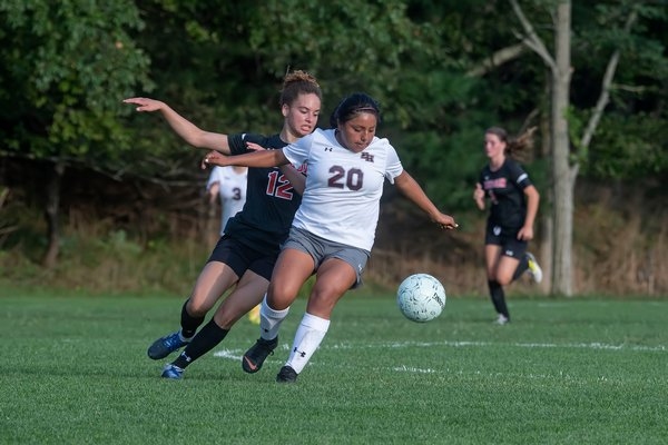 Pierson senior Chastin Giles and East Hampton junior Jessica Guallpa both go for the ball.