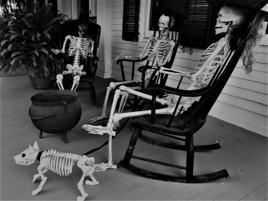 Four skeletons on the porch of the haunted Rogers Mansion.